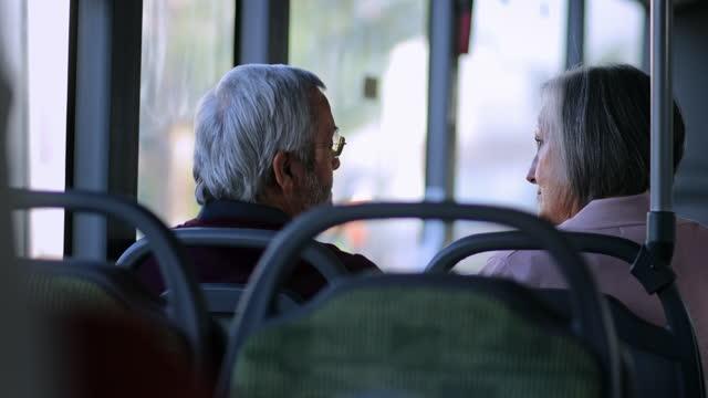 coppia anziana che parla insieme viaggiando all'interno dell'autobus - dorso umano video stock e b–roll