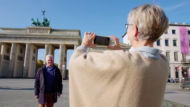 Senior couple traveling to Berlin taking photos
