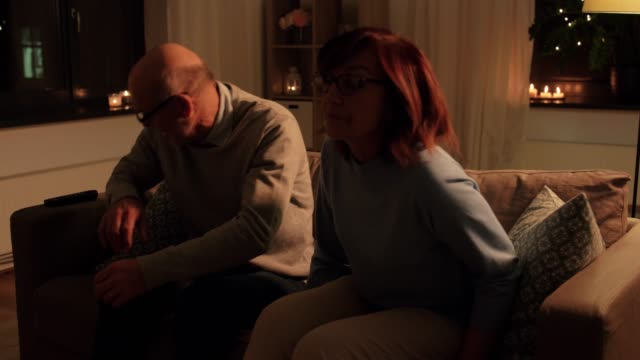 senior couple turning tv on at home in evening - vídeo