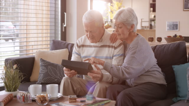 ds senior couple using a digital tablet on the sofa - coppia anziana video stock e b–roll