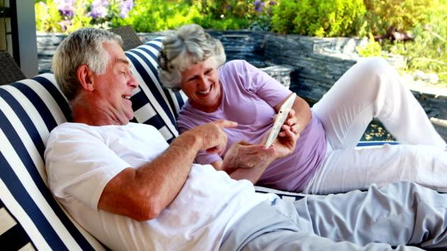 Senior couple using digital tablet 4k video