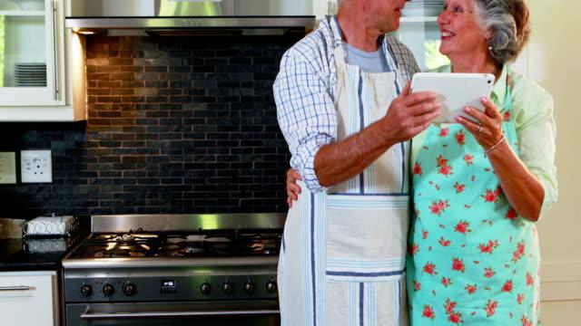 Senior couple using digital tablet in kitchen 4k video