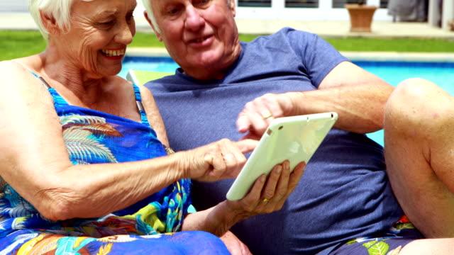 äldre par med digital tablett på solstol - sarong bildbanksvideor och videomaterial från bakom kulisserna