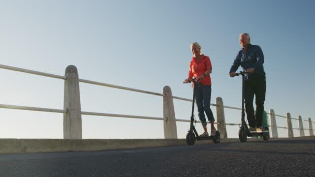 Senior-Paar mit elektronischen Rollern am Strand – Video