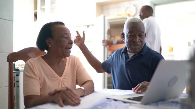 Senior couple using laptop at kitchen Senior couple using laptop at kitchen financial planning stock videos & royalty-free footage