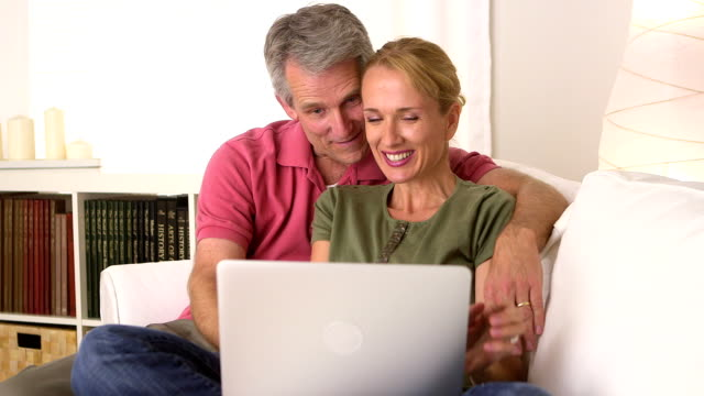Senior couple using laptop  on the couch video