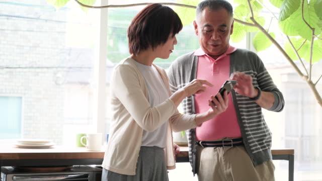 vídeos y material grabado en eventos de stock de pareja de edad mayor utilizando teléfono inteligente - casados