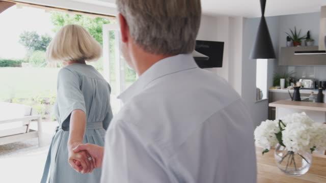 senior paar gehen aus der küche und durch terrassentüren, um garten zu sehen - grundstück stock-videos und b-roll-filmmaterial