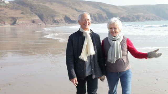 Senior Couple Walking Along Winter Beach video