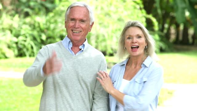 Senior couple walking, holding hands, talking video