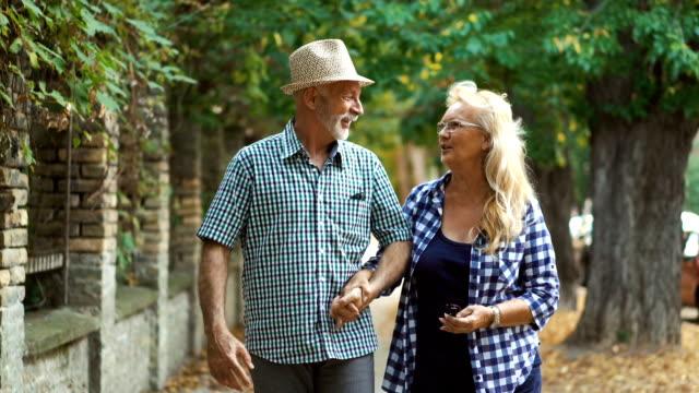 senior par som går på gatan. - aktiva pensionärer utflykt bildbanksvideor och videomaterial från bakom kulisserna