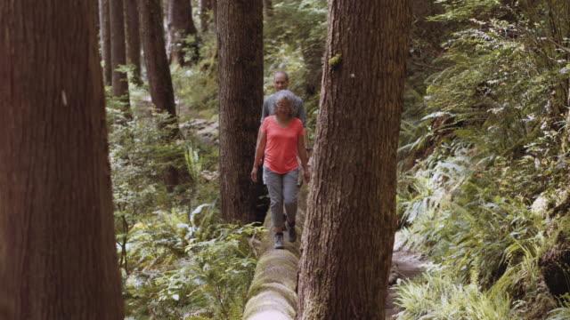 Senior couple walking on a log through the woods video