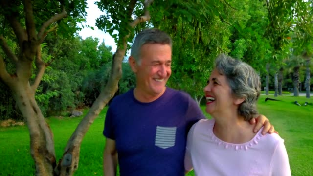 senior couple walking on the park, having fun, laughing and talking. - 50 54 lata filmów i materiałów b-roll