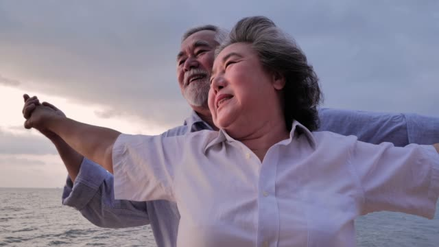 Senior couple watching sun set over ocean.Senior couple relaxing by the sea on sunny day ,Senior Holidays