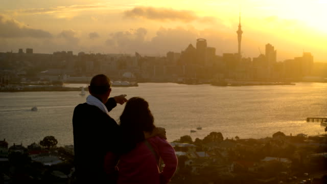Couple de personnes âgées regardant le coucher de soleil dans la ville de Auckland - Vidéo