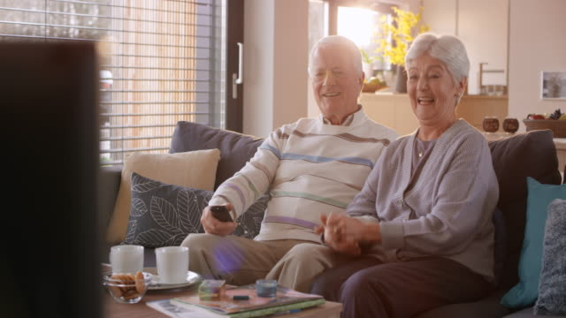Senior couple watching TV, singing and laughing video