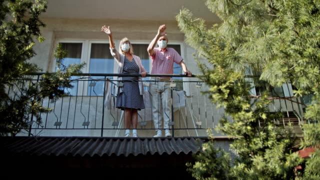 vídeos de stock e filmes b-roll de senior couple waving from balcony during covid-19 quarantine - isolated house, exterior
