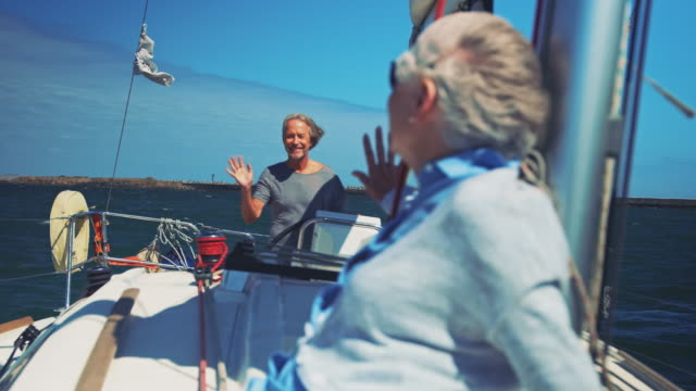 Senior couple waving hands at each other in yacht