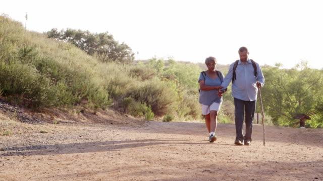 äldre par bär ryggsäckar vandring i landsbygden tillsammans - senior walking bildbanksvideor och videomaterial från bakom kulisserna