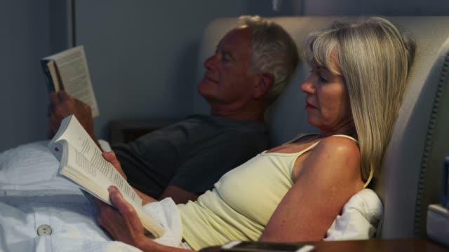 stockvideo's en b-roll-footage met senior paar dragend pyjama's liggend in bed lezen - woman home magazine
