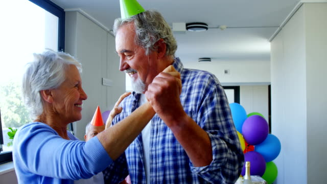 senior couple wearing party hats dancing at birthday party 4k - 60 69 anni video stock e b–roll