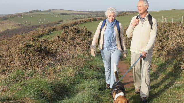 Senior Couple With Dog Walking Along Coastal Path video