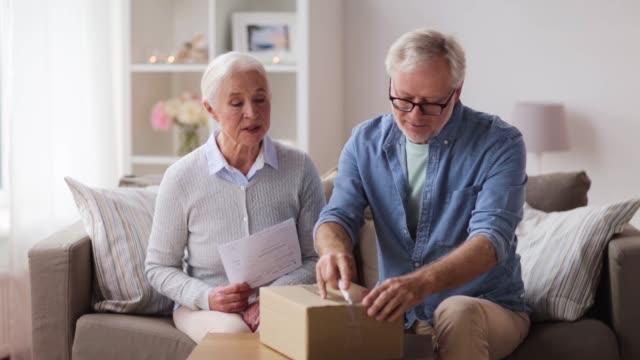 senior couple with parcel and delivery note - confezione video stock e b–roll