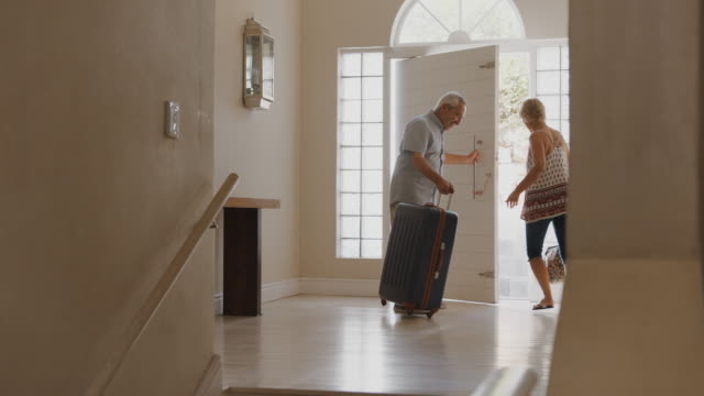 Senior Couple With Suitcase Opening Front Door And Leaving For Vacation