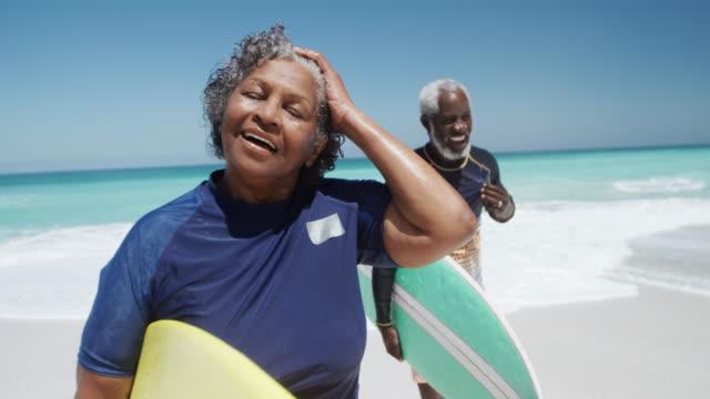 seniorenpaar mit surfbrettern am strand - aktiver senior stock-videos und b-roll-filmmaterial