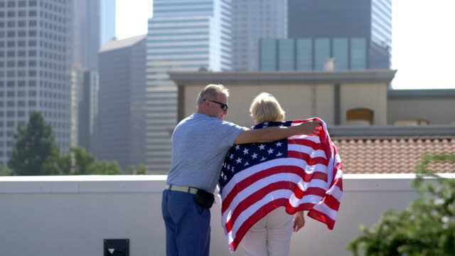 Senior Couple with USA flag on the rooftop in Los Angeles in 4K Slow motion 60fps
