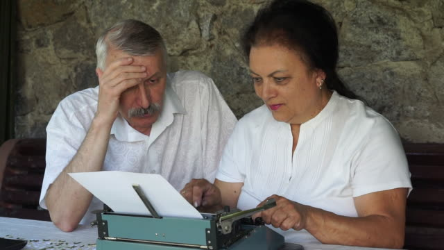 senior couple writing traditional mail by typewriter