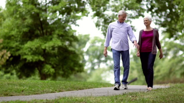stockvideo's en b-roll-footage met senior couples walking in park - oudere volwassenen