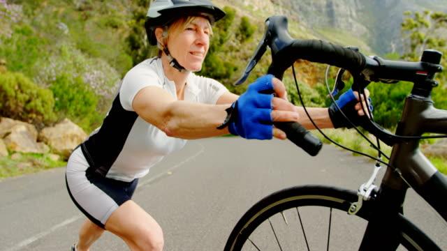 senior cyclist exercising with cycle at countryside 4k - rozgrzewka filmów i materiałów b-roll