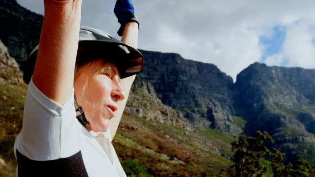 vídeos de stock e filmes b-roll de senior cyclist standing with arms up at countryside 4k - 55 59 anos