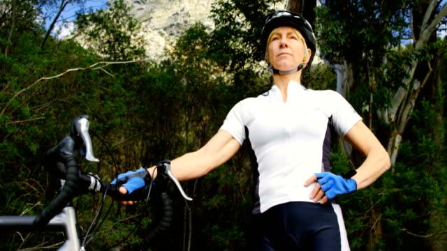 vídeos de stock e filmes b-roll de senior cyclist standing with bicycle at countryside 4k - 55 59 anos