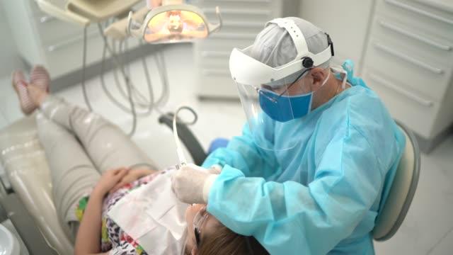 vídeos y material grabado en eventos de stock de dentista sénior examinando los dientes de una mujer joven - dentista