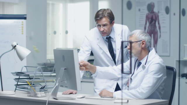Senior Doctor and His Assistant Discuss Patient's Log on Personal Computer. ビデオ