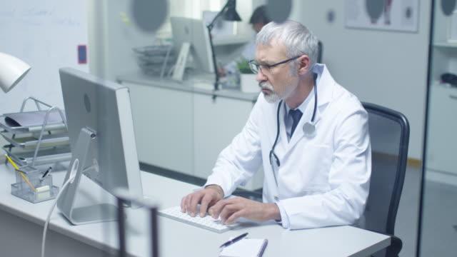 Senior-Arzt und seinem Assistenten arbeiten bei Desktop-Computern. Sitzen in hell beleuchteten Büro. – Video