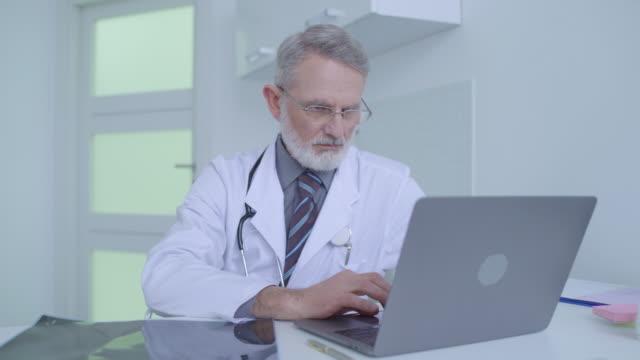 stockvideo's en b-roll-footage met hogere arts die hersenen mri scan controleert, het typen diagnose op laptop, geneeskunde - medische röntgenfoto