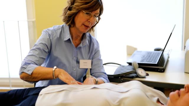 oberarzt überprüft patienten in klinik - menschlicher verdauungstrakt stock-videos und b-roll-filmmaterial