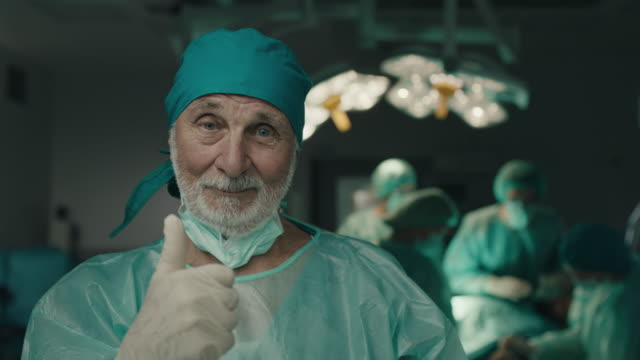 Senior doctor showing thumbs up Senior doctor smiling and showing thumbs up in operating room satisfaction stock videos & royalty-free footage