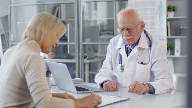 senior doctor signing agreement and shaking hands with female patient - firmare video stock e b–roll