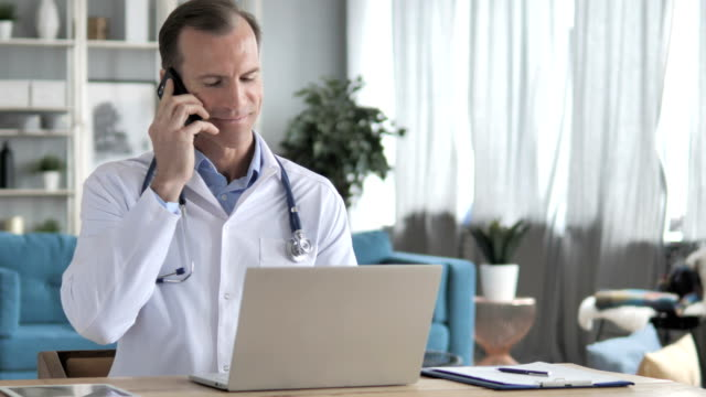 senior doctor talking on phone with patient in clinic - rispondere video stock e b–roll
