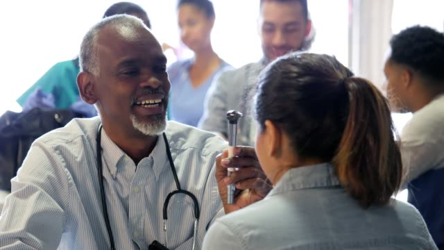 Senior doctor tests woman's eyesight in free clinic Confident African American senior volunteer doctor examines a mid adult woman in free clinic. He is holding an otoscope while having the woman follow his finger with her eyes. Doctors are in the background examining patients. eye exam stock videos & royalty-free footage