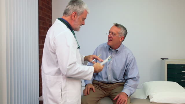 Senior Doctor Visit A senior man talking with his doctor in an exam room. test results stock videos & royalty-free footage