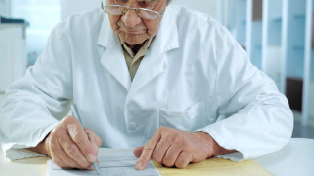 Senior doctor writing down the diagnose video
