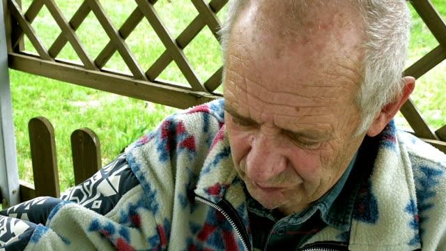 Senior elderly man eats and drinks tea on patio video