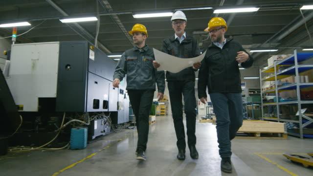 シニア エンジニアと 2 人の労働者は、工場スペースでペーパーで歩いています。 ビデオ