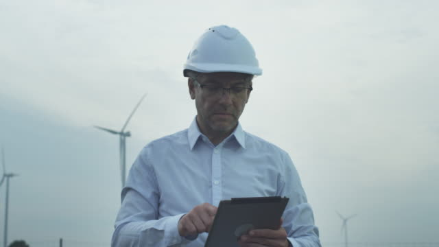 Senior Engineer in Hard Hat using Tablet Computer Outdoors. Wind Turbines on Background.