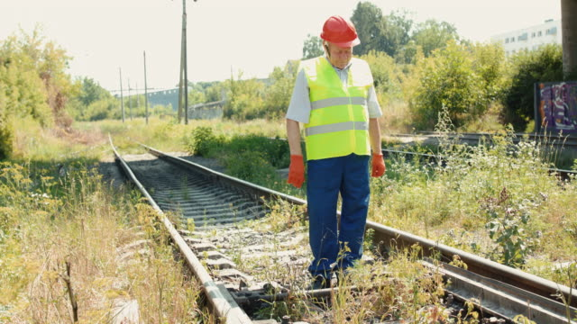 Senior engineer in uniform and helmet checks the railway in sunny day video